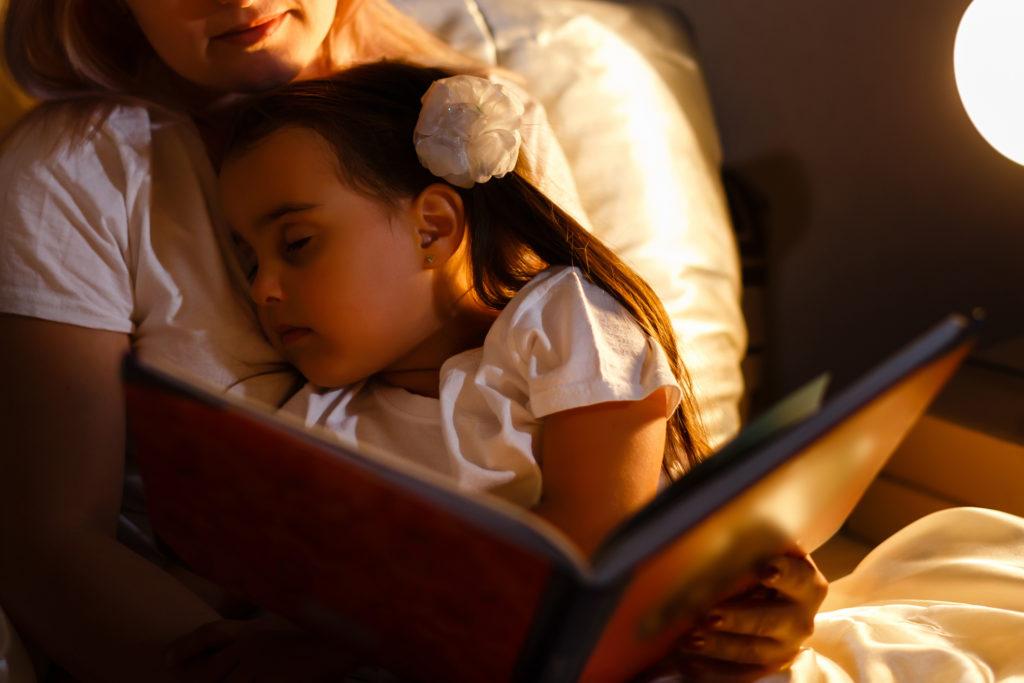 Lapsi on nukahtanut sängyssä kumminsa syliin kesken iltasadun.