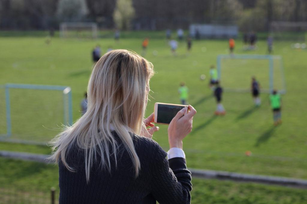 Kummi on seuraamassa kummilapsensa jalkapallopeliä ja ottaa kuvia kännykällä.