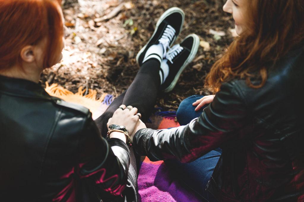Teinityttö ja hänen kumminsa hymyilevät ja pitävät toisiaan kädestä.